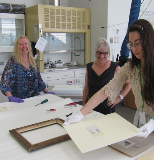 Sabine Schaefer, Art Handler, delivers works on paper to Maureen Del Degan, Collections Care Specialist and Elizabeth Carroll (handling matted work of art using cotton gloves)