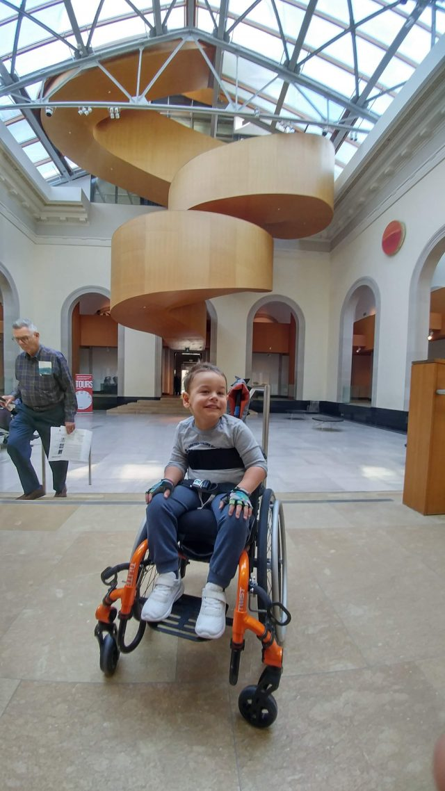 Small boy in wheelchair in the AGO's Walker Court