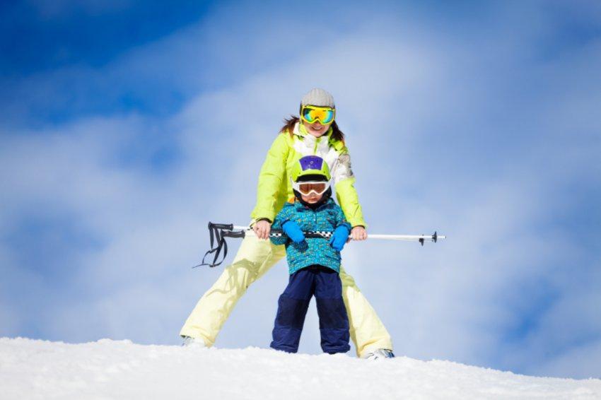 Un jeune enfant apprenant à skier grâce à l'aide de son moniteur de ski.