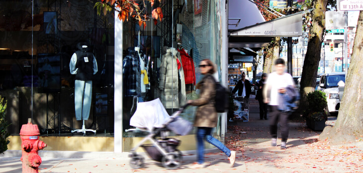 Person pushing a stroller on the sidewalk in front of a clothing shop
