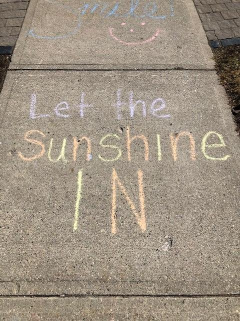 Chalk drawing on a sidewalk that says Let the sunshine in