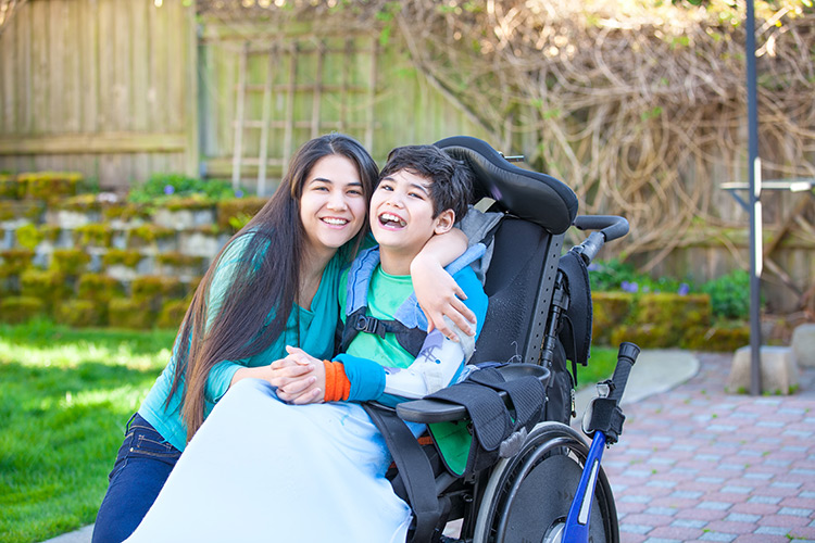 Teenage girl hugging brother in wheelchair outside in the backyard
