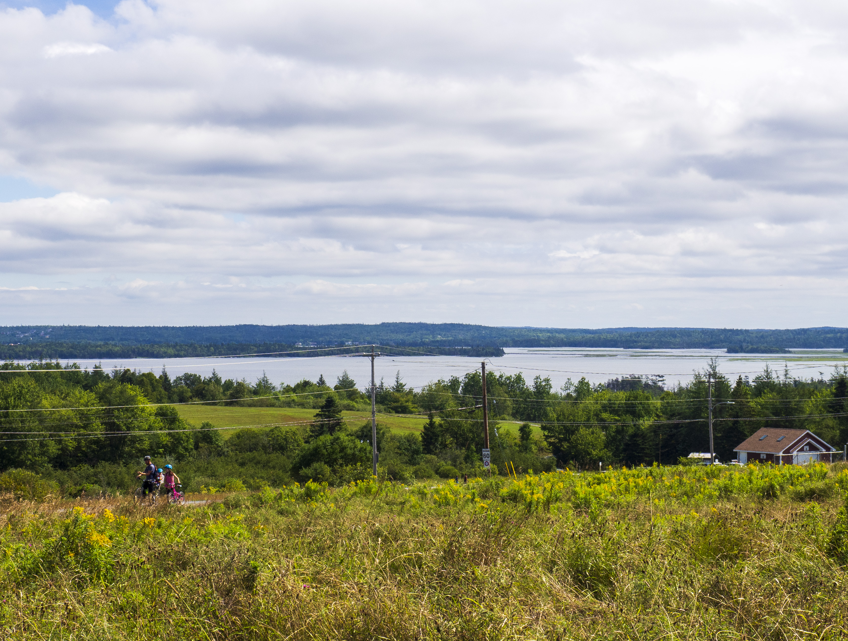 Landscape vista looking east from the hilltop with family cylcing in the foreground and the Cole Harbour Basin in the background.