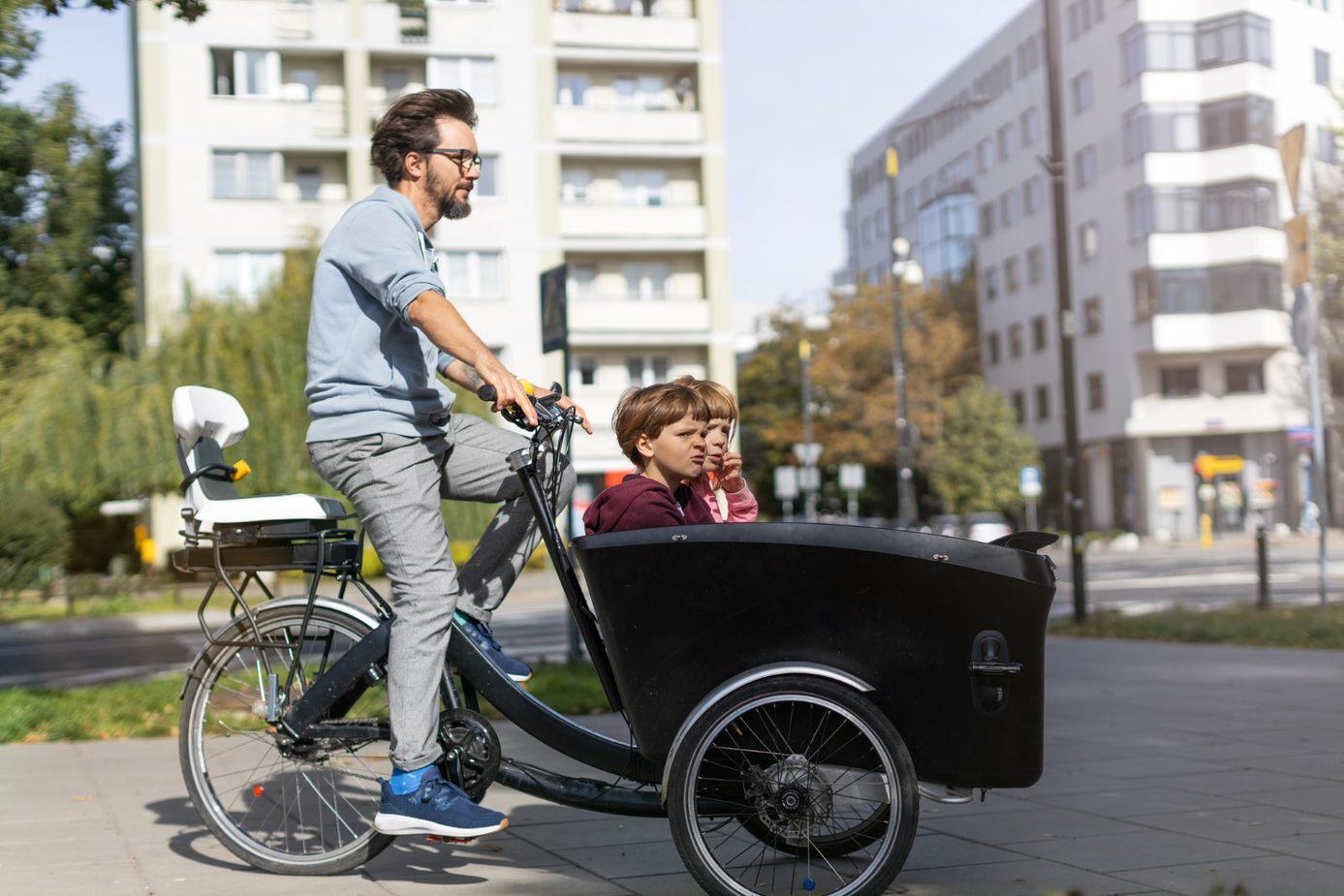 Homme avec enfants dans un panier d'un vélo cargo électrique personnel