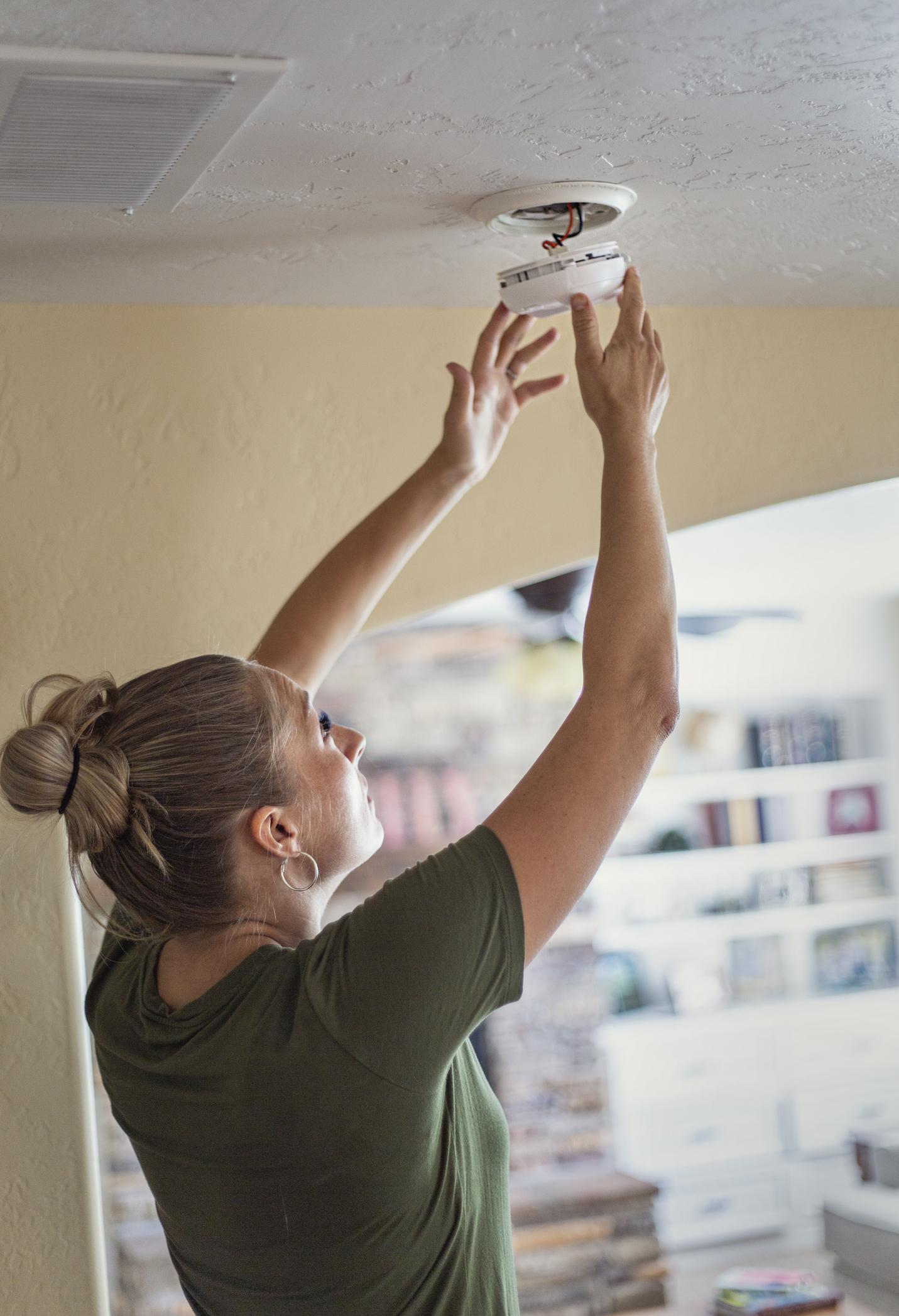 Woman installing a smoke alarm