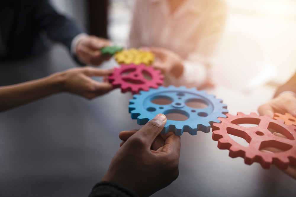hands holding coloured gears