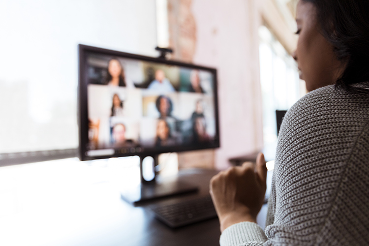 Woman sits in front of a computer screen for a video chat