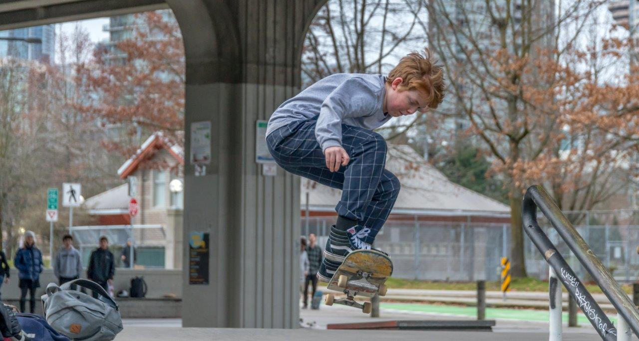Youth performs a skateboard trick with onlookers in the background