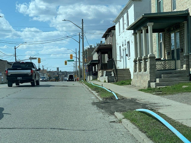 Temporary water pipe on ground behind curb