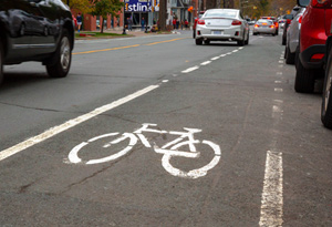 Current South Park Street bike lane near the Spring Garden Road intersection, with cars parked on the right hand side and road traffic on the left hand side.