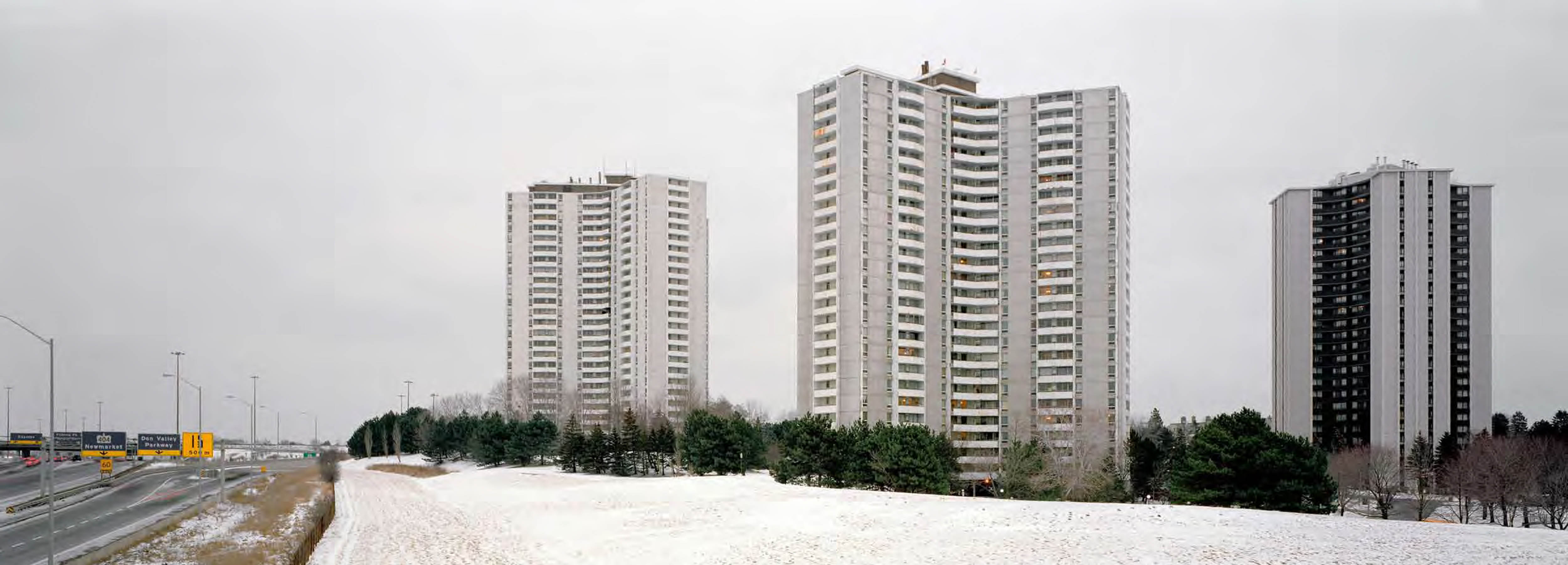 Tall apartment towers surrounded by trees and snow-covered lawns next to a highway