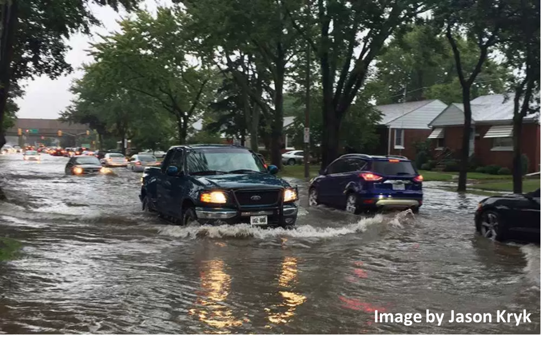 Image of a flooded street with cars driving on. Image by Jason Kryk.