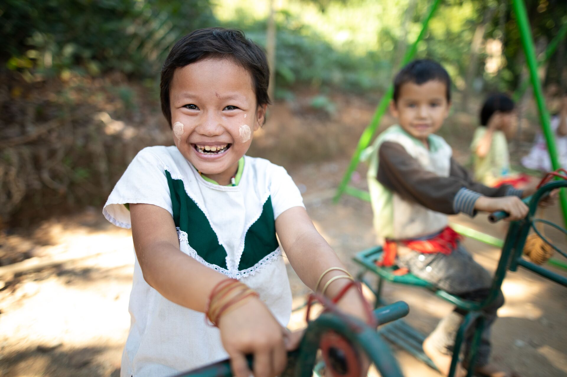 A Thai child in a white and green shirt plays on a playground structure. Other children are in the background.