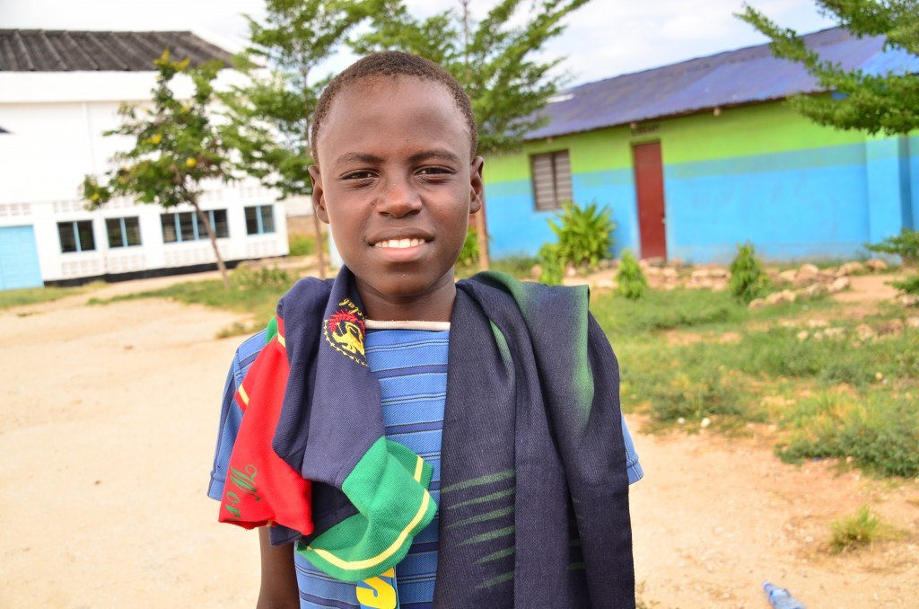 A boy smiles in a close-up with his new clothes on his shoulders