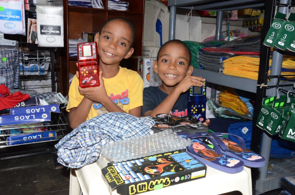 Amauris Jimenez Jimenez and Adoni Jimenez Jimenez smile together standing in a store holding toys on a table with games and clothes