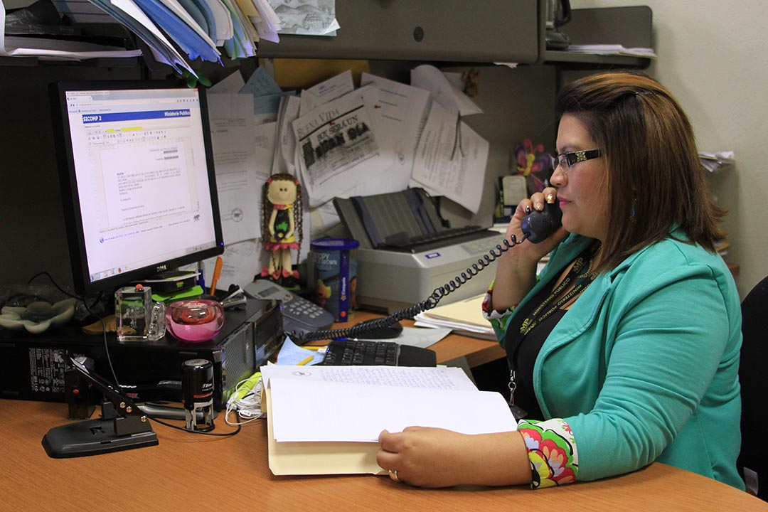 Leticia Judith Ochoa Contreras, adult woman, wearing a green shirt, glasses, sits at her office desk and works in the Public Prosecutor's Office in the Abuse Women and Children's area, holds a phone to her head, speaking on the phone, working, looking at computer screen, monitor, computer, keyboard, office desk space.