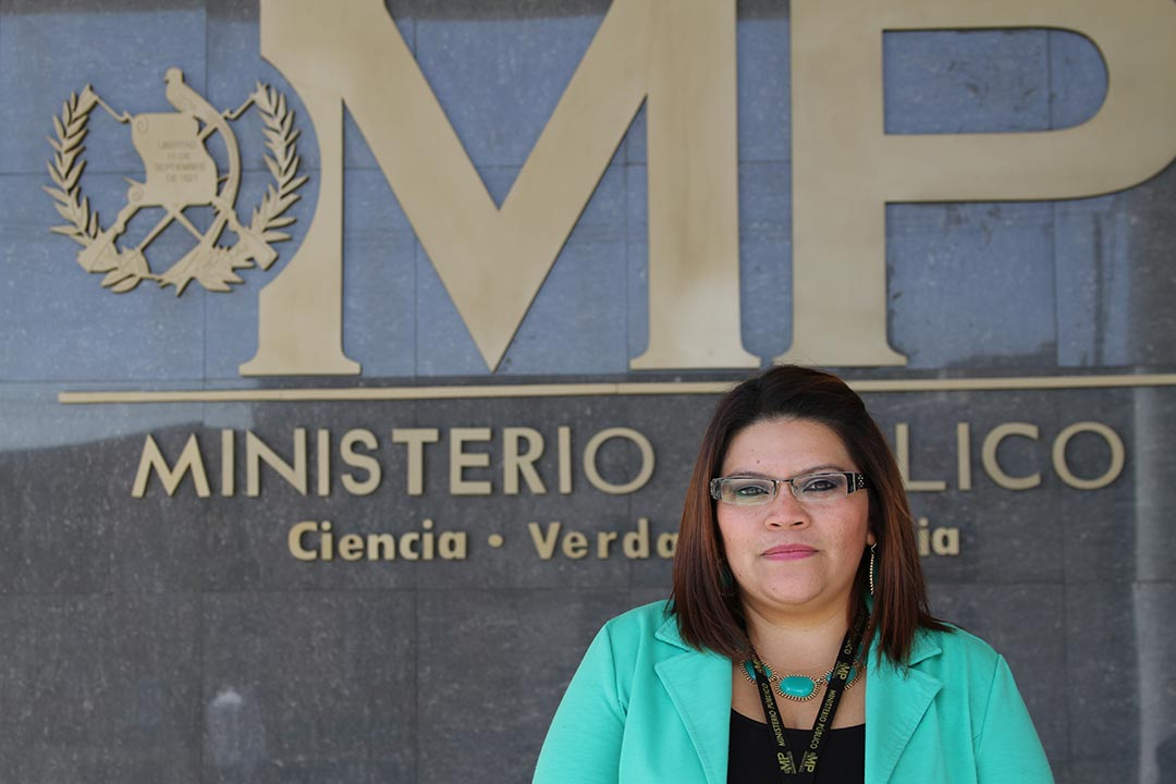 """Leticia Judith Ochoa Contreras, adult woman, wearing a green shirt, glasses, works in the Public Prosecutor's Office in the Abuse Women and Children's area, and stands outside in a portrait close-up, """"Ministerio Público, Ciencia, Verdad y Justicia"""" which means """"Public Prosecutor's Office, Science, Truth and Justice"""""""