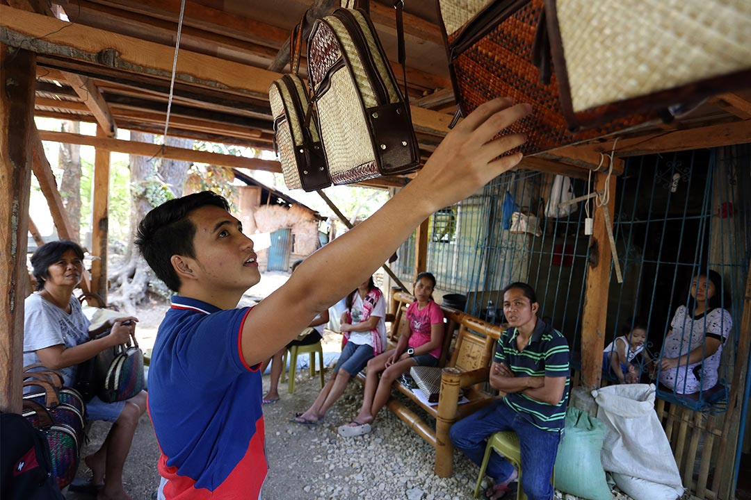 Jeric stands in an open air store front. He's inspecting hand made bags and talking to the people that sit nearby