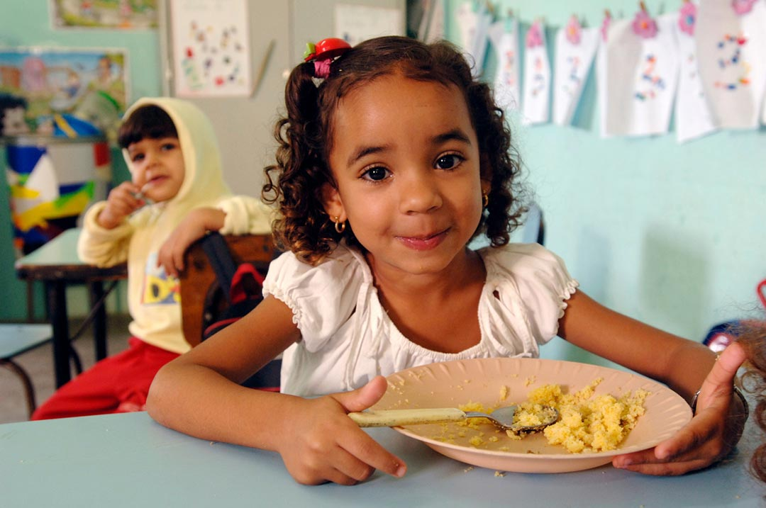 A little girl sits at a table eating rice. She's smiling