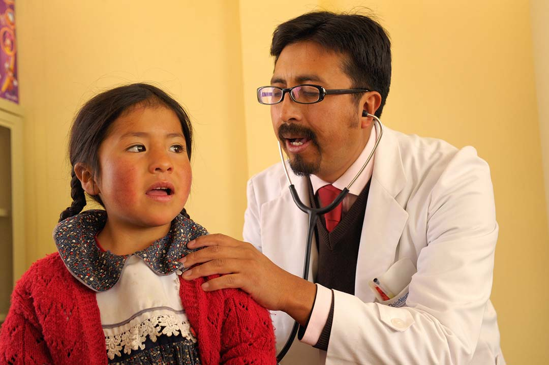 A doctor uses his stethoscope to listen to back of a little girl in a red sweater.