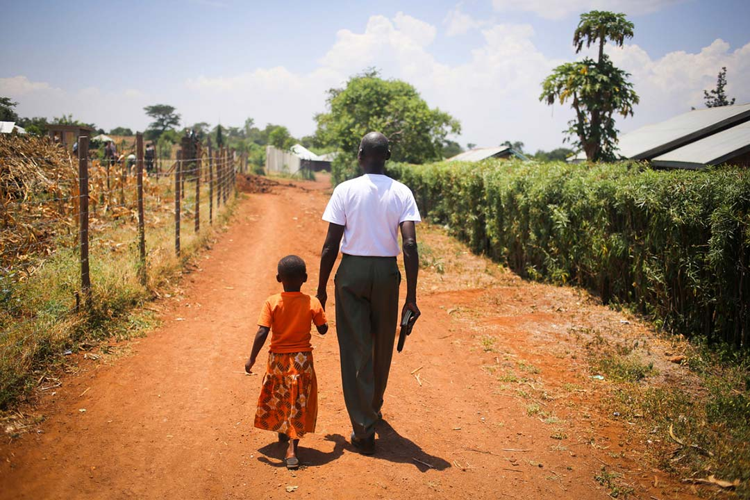 A little girl walks down the road, holding the hand of a grown man. The man is holding a bible in his other hand.