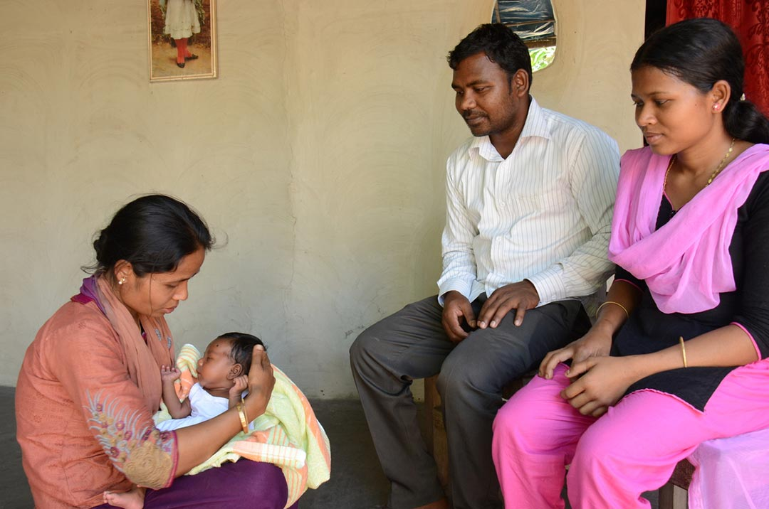 A mother and father sit and look on as woman holds their baby, showing them how to care for their infant properly