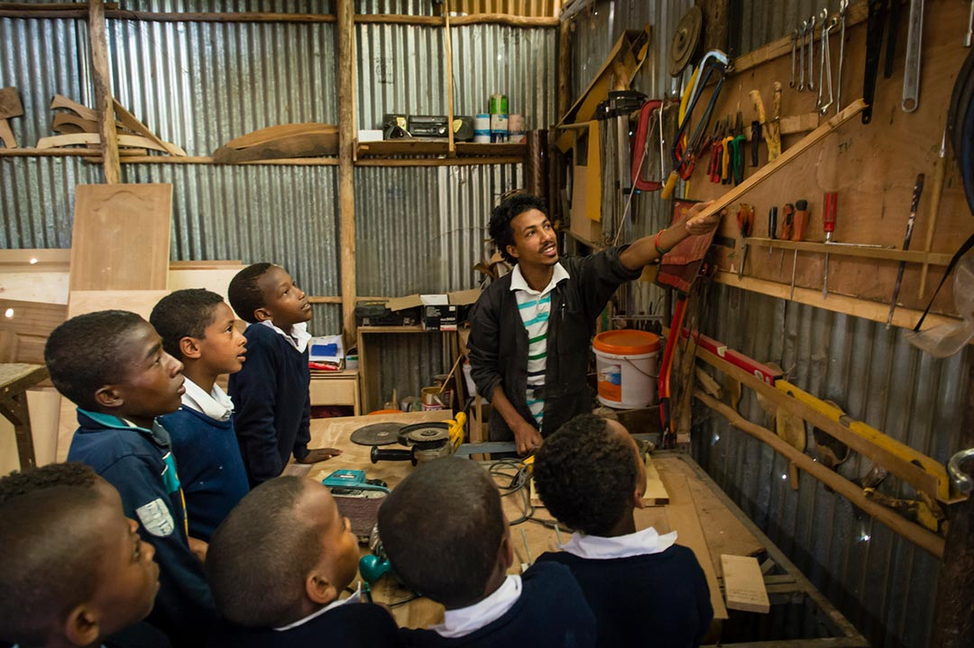 A young teacher uses a long piece of wood to point to different tools hanging on the wall. A number of carpentry students look on.