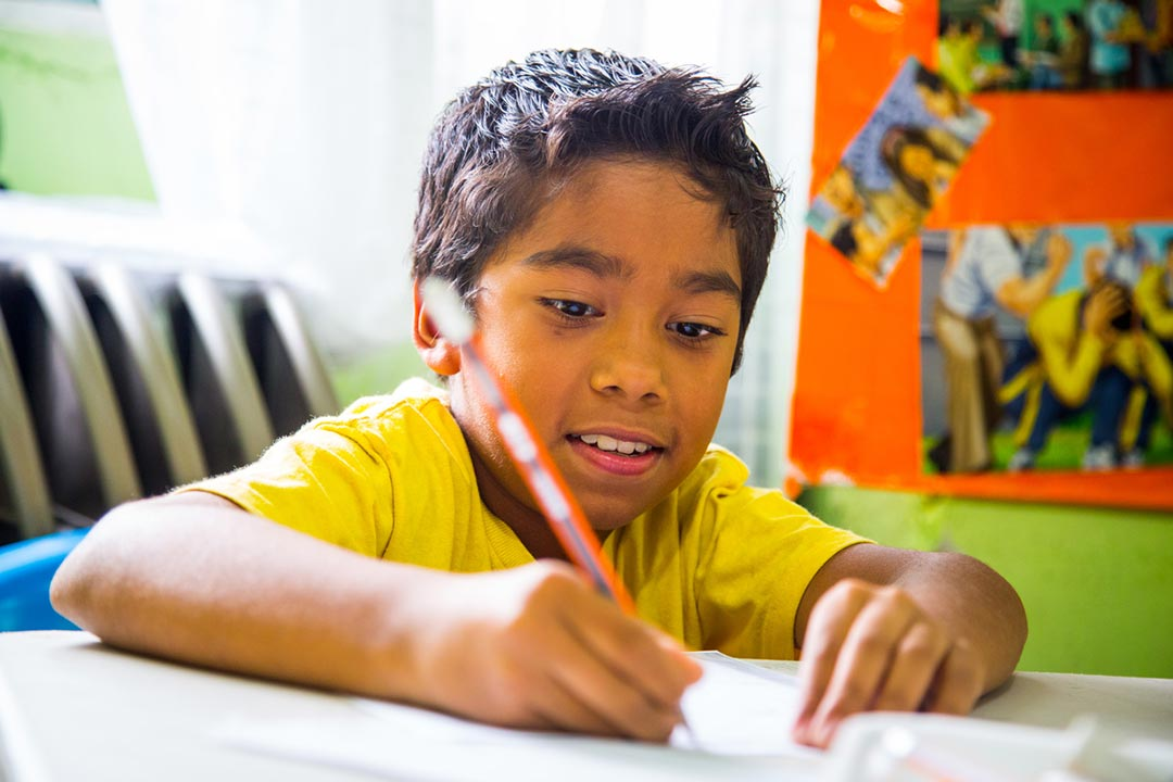 A little boy sits at a desk writing on a piece of paper