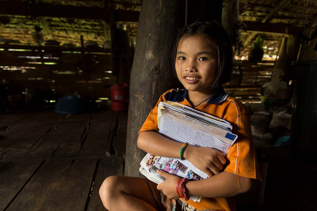 A girl sits in her grass hut holding a large pile of letters from her sponsor. She looks proud and confident.