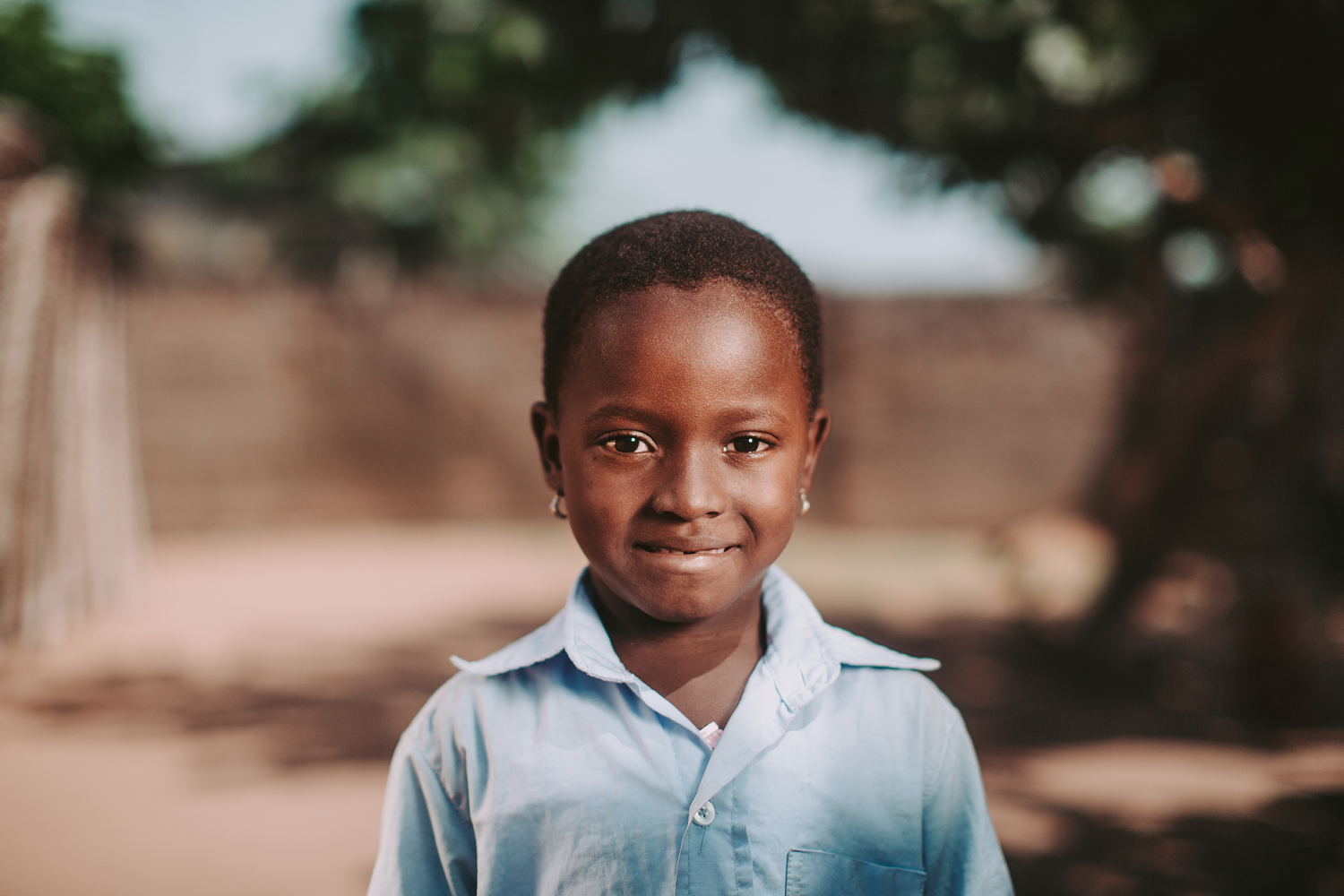Aklobessi, a four year-old girl living in Togo, looks at the camera as she sits on a bench in a Compassion Centre.