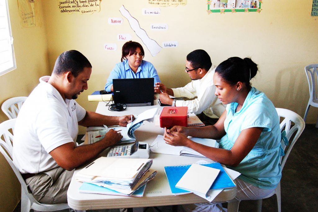 A woman sits at a table at a child centre and does paperwork with a team of two men and one other woman.