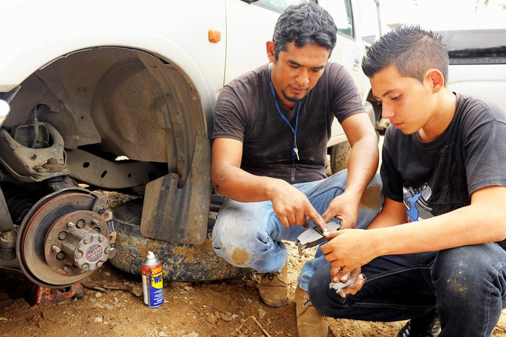 A male mentor shows a teenage boy how to work brakes on a truck.