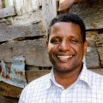 Pablo, now a pastor and director of a Compassion centre, stands in front of a wall and smiles.