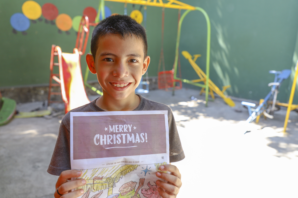 A boy holds up a letter with the heading 'Merry Christmas!'