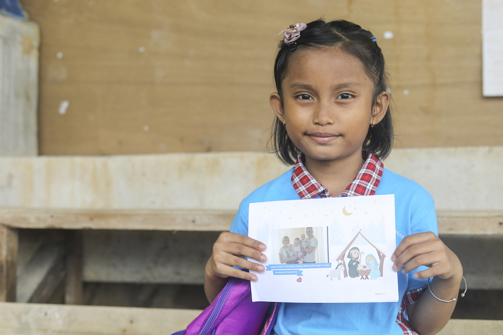 A girl holds up a photo of her sponsors, in a Christmas card.