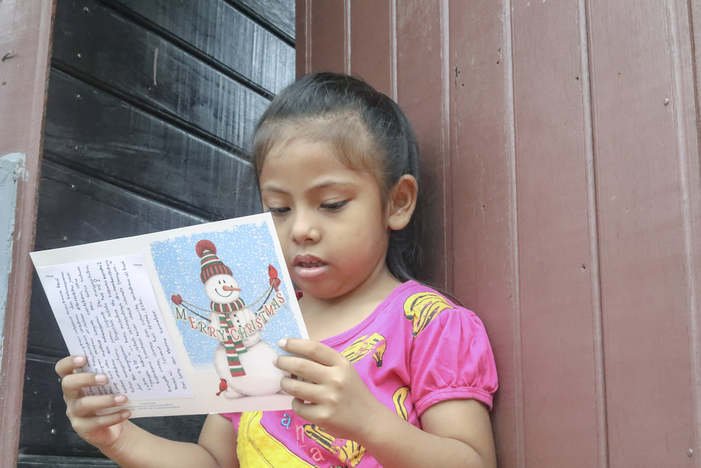 A girl reads a Christmas card from her sponsor.