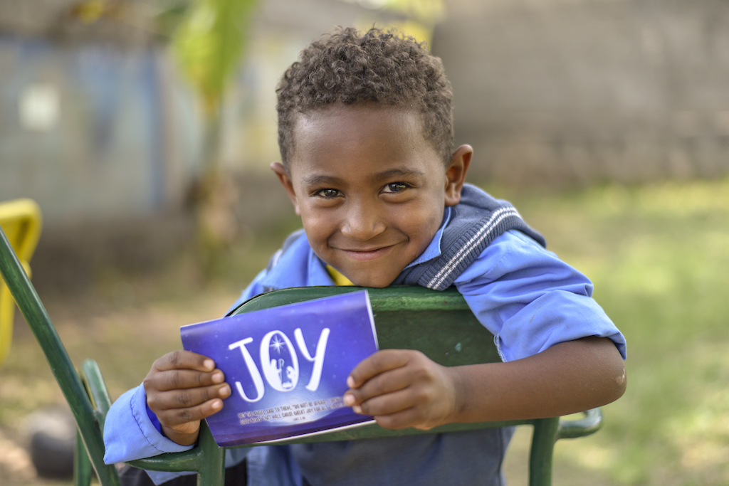 """A boy sitting on a chair holds up a Christmas card that says """"JOY"""" on the front."""