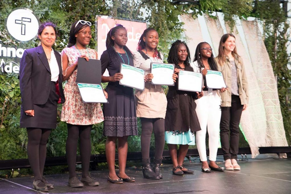 Five girls stand on stage receiving a technovation award from the presenters.
