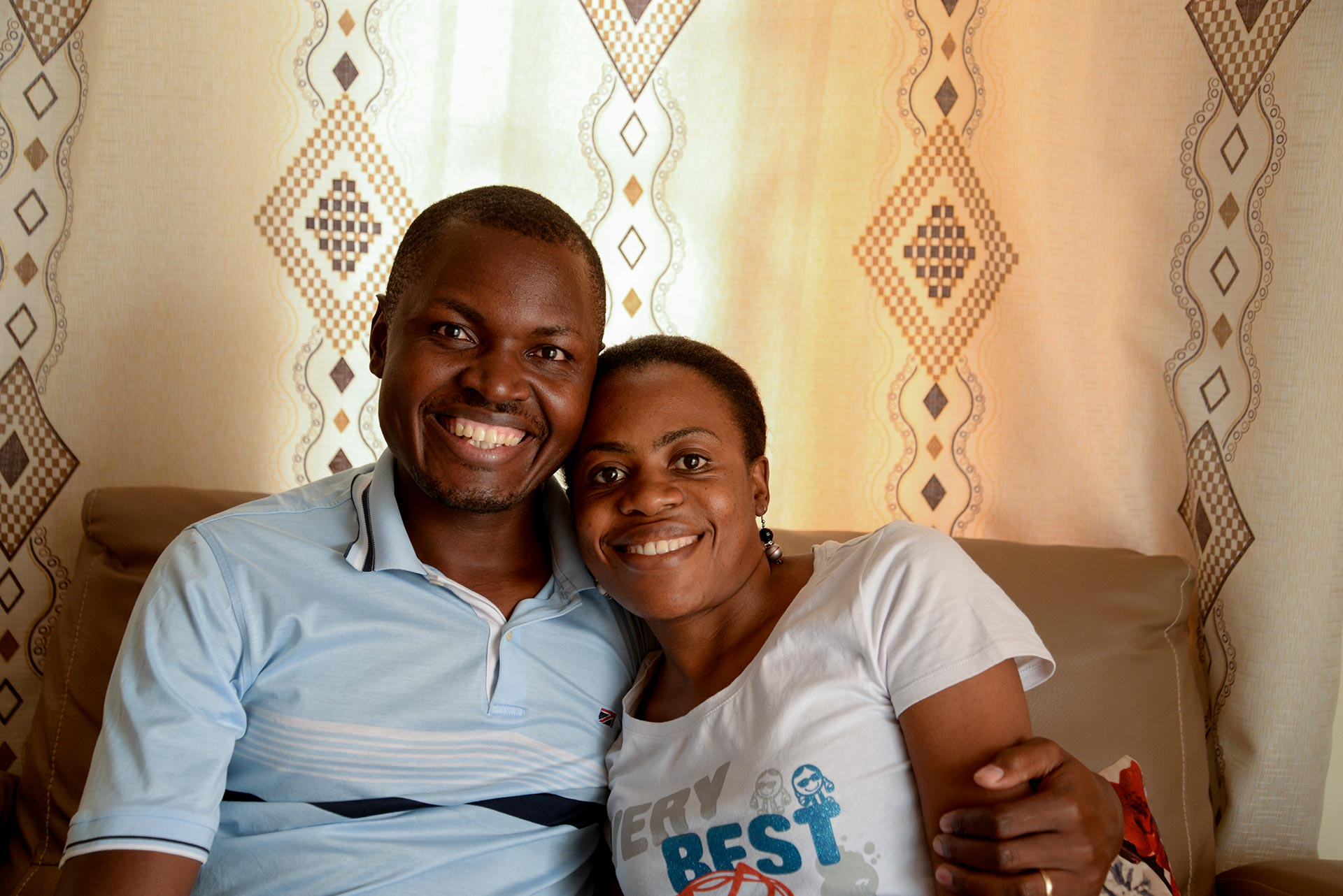 A Ugandan man and woman sit together on a couch and smile.