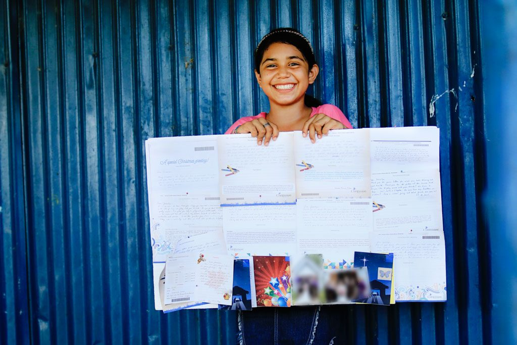 A girl stands infront of a blue, corrigated metal wall and holds up a poster made out of all her sponsors letters.