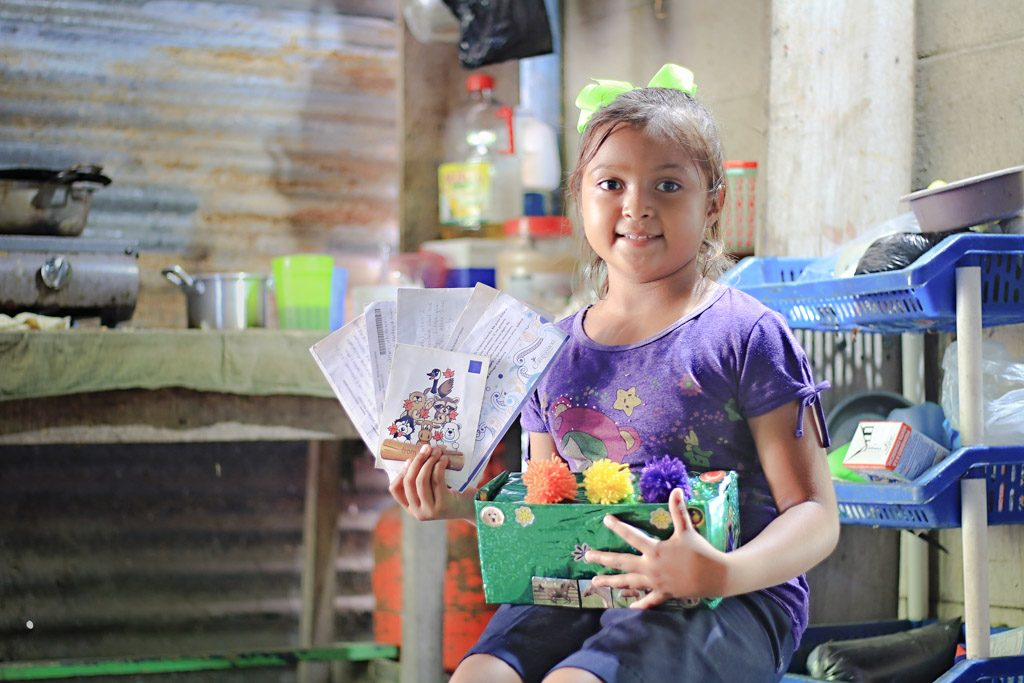 A little girl sits in a kitchen holding a shoe box full of letters and gifts from her sponors.