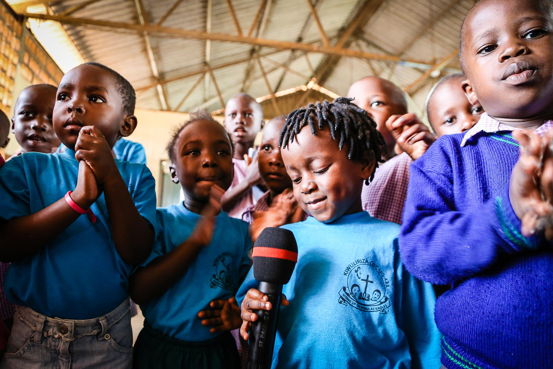 A child looks down at a microphone as other children crowd around.