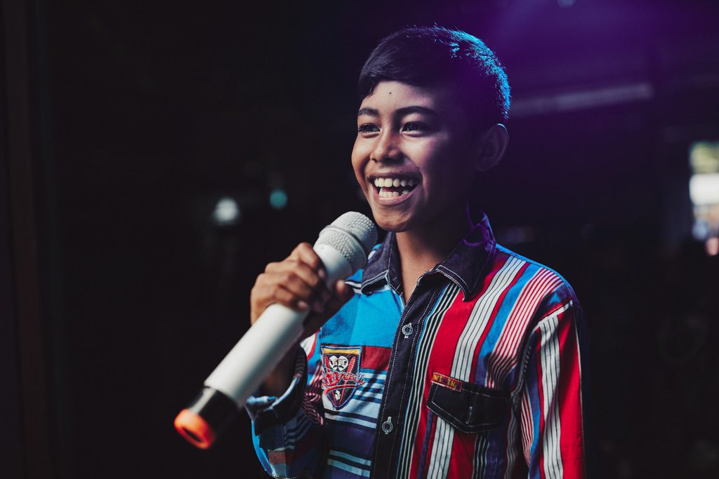 A happy boy, male child in a red, white, blue striped shirt holds a white microphone, sings, singing with stage lights behind him.