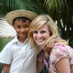 A boy and his sponsor are smiling together. They are standing together outside in front of the trees. The woman has blonde hair and the little boy is wearing a straw hat.