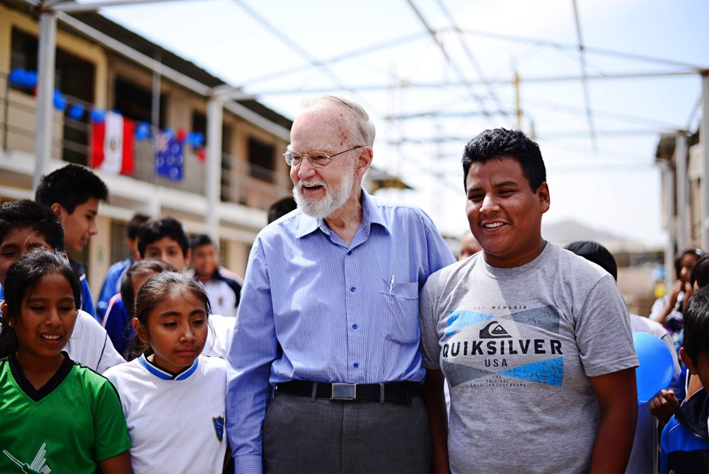 An older man stands at a child center surrounded by kids and leaders.