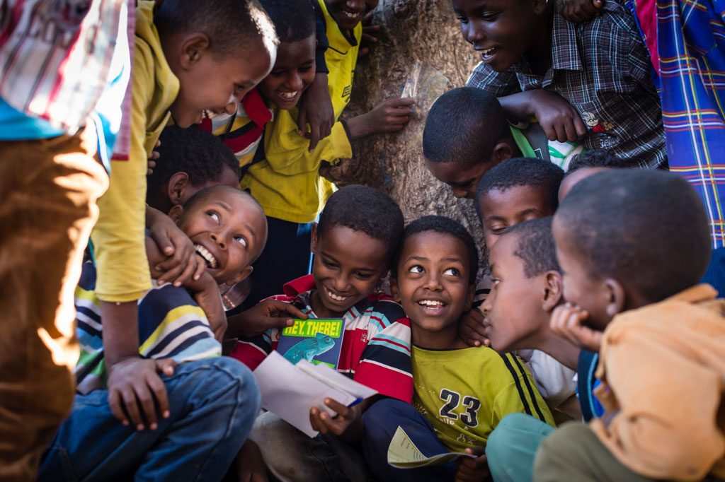 A group of young boys crowd around eachother, smiling and laughing as they read eachother's sponsor letters.