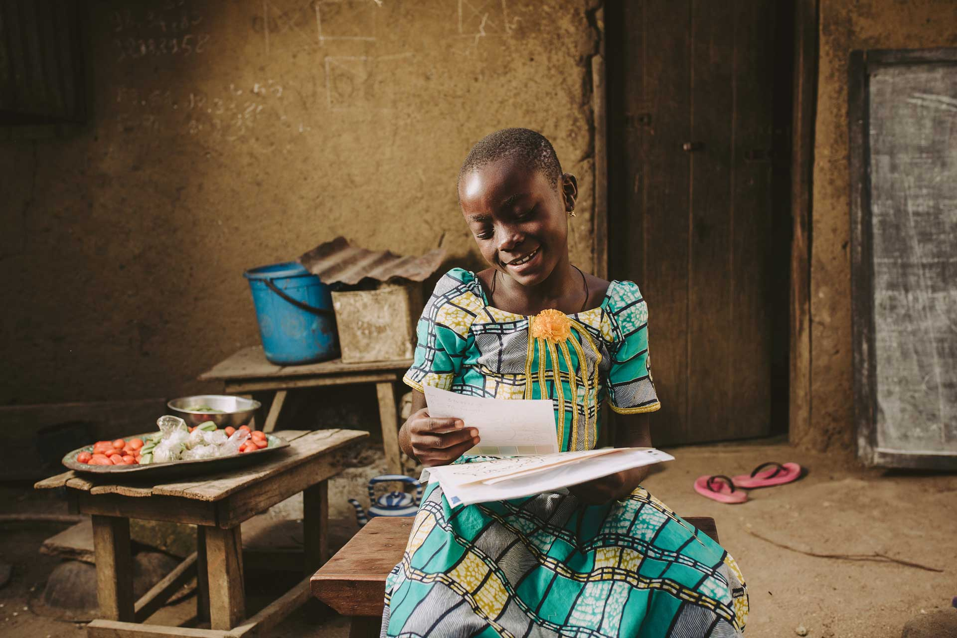 A young girl from Togo, in an ornate green dress, reads a letter from her sponsor.