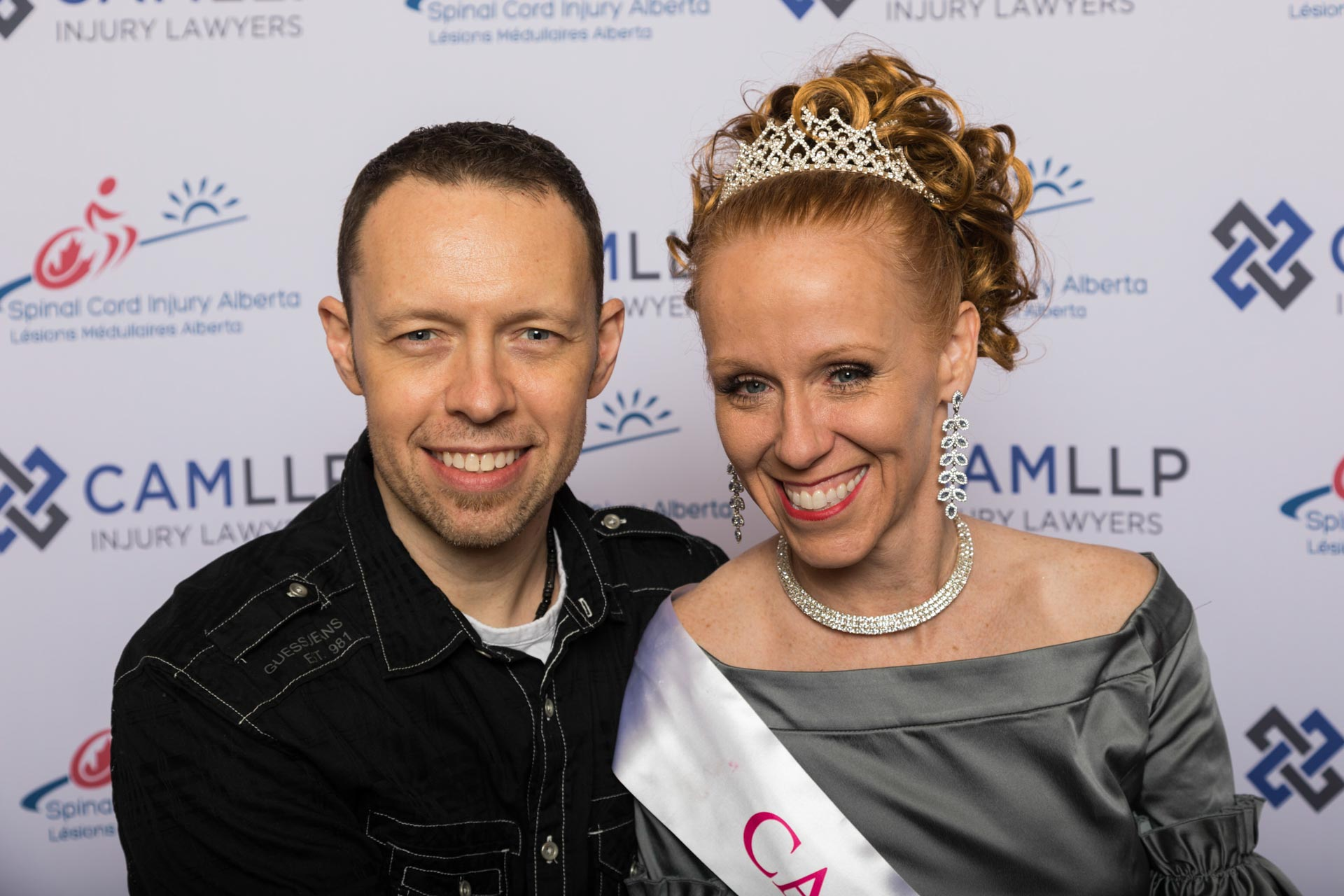 Vahen and her husband pose in front a red carpet backdrop at the Miss Wheelchair Canada awards. Vahen wheres a teirah and smlies at the camera.