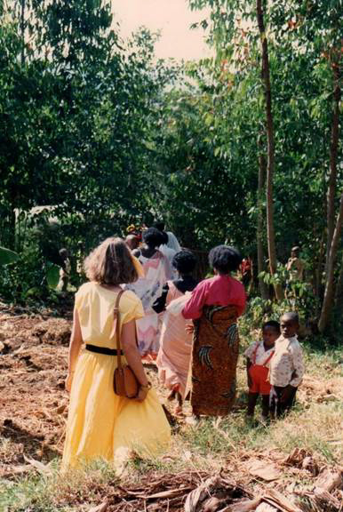 Two young Rwandan boys stand beside a forest trail as visitors and locals walk by.