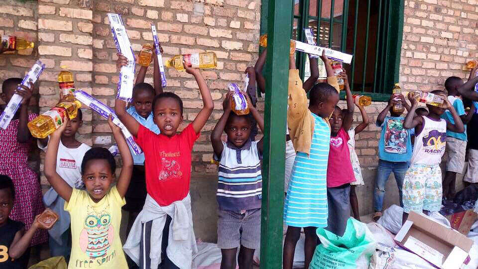 Kids stand on a porch and hold up different supplies that were givent to them.